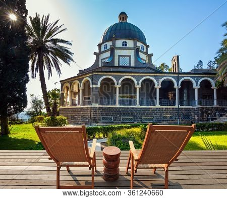 Two comfortable wooden chairs - deck chairs for relaxing on the platform. Catholic Church of the Beatitudes and park around the monastery. The concept of religious pilgrimage and photo tourism