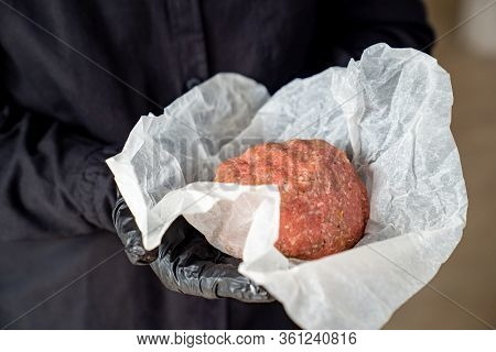 The Minced Meat On The Cooking Paper In The Hands Of A Man With Black Gloves. Prefabricated Patties.