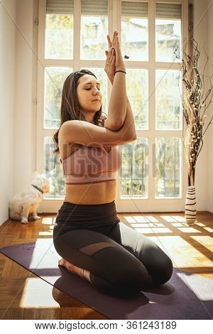 Young Woman Is Relaxing During Coronavirus Pandemic Doing Yoga Meditation In The Living Room At Home
