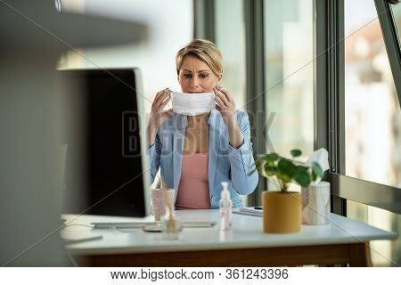 Business Woman In A Medical Protective Mask Works At The Office On The Computer During Self-isolatio