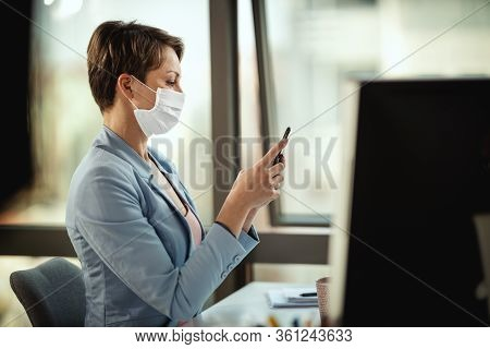 Business Woman In A Medical Protective Mask Typing Message At The Smartphone And Works At The Comput