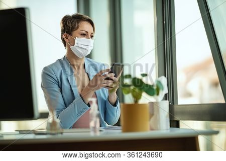 Business Woman In A Medical Protective Mask Works From Home At The Computer, Using Smartphone, Durin