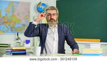 Back To School. Knowledge Day. Man School Teacher Sit In Classroom. Handsome Mature Smart Educator.