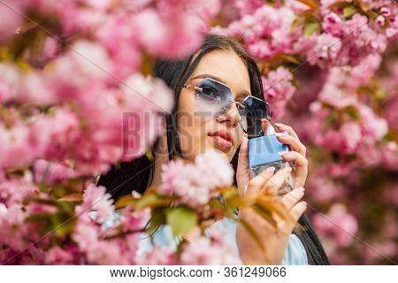 Luxury Fragrance. Fashionable Woman Hold Perfume Bottle. Cherry Blossom Aroma. Female Perfume. Sprin