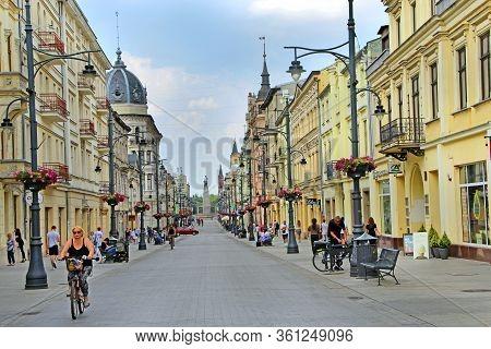 Lodz / Poland. 14 July 2019: Tourist On Bike Next To Rickshaw On City Street. Young People Walking A