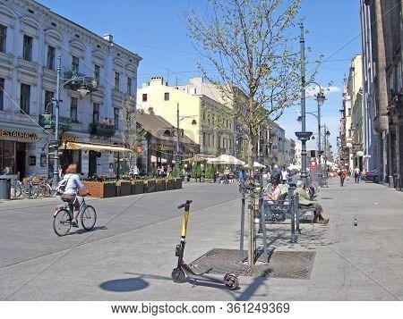 Lodz / Poland. 18 July 2019: Tourist On Bike Next To Rickshaw On City Street. Young People Walking A