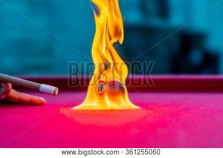 Billiard balls are photographed on fire while sitting outdoors in an open environment