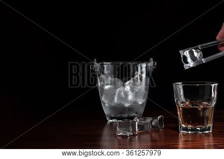 Hand With Tongs Holding Ice-cube Above A Glass With Whiskey, Ice Bucket Behind The Alcoholic Drink O