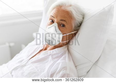 medicine, health safety and pandemic concept - senior woman patient lying in bed wearing face protective mask or respirator for protection from virus disease at hospital ward