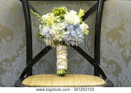 Blue Hydrangeas And White Flower Bouquet On A Chair For A Wedding Ceremony