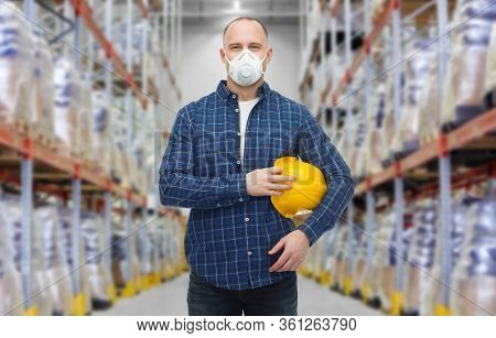 health care, work and pandemic concept - male worker with safety helmet wearing face protective mask or respirator over warehouse background