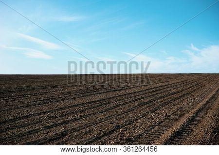 Plowed Field In Spring. Agricultural Rural Background. Plowed Soil.