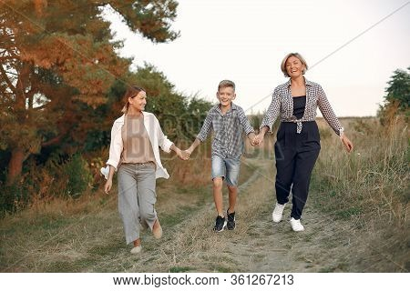 Two Mothers With Young Son Walking In A Spring Field