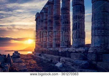Greece Cape Sounio. Ruins of an ancient temple of Poseidon, Greek god of the sea, on sunset. Shot of temple ruins on sunset. Tourist landmark of Attica, Sounion, Greece