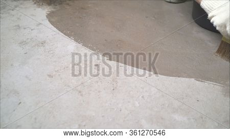 Stage Of Waterproofing The Floor. The Master Soaks The Concrete Floor With Water Using A Brush. Prim