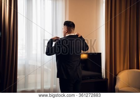Young Handsome Businessman Adjusting His Jacket Dressing Up At His Luxury Hotel Suite Preparing For