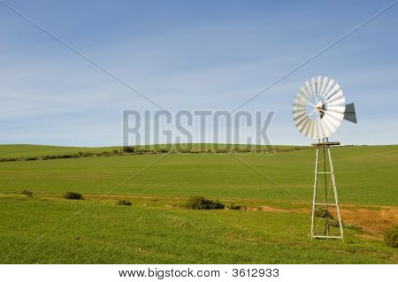 A traditional windmill turning in the wind and pumping water out of the ground into a catchment dam. poster