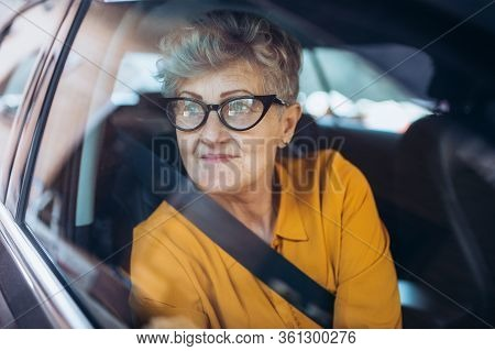 Senior Woman With Glasses Sitting In A Car. Shot Through Glass.