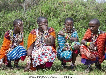 Africa, Kenya, Masai Mara, March, 2016 - Masai Women In Multi-colored Cotton Dresses And Beaded Jewe