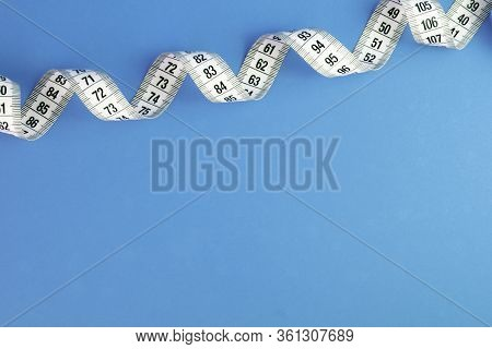 Unfolded White Tape Measure, White Measuring Tape Isolated On Blue Background. Close The Tailor Meas