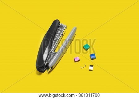 Metal Black Stapler With Braces Nearby Lying On A Yellow Background . Concept Of Office Chancery. Fr