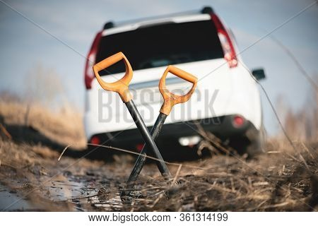 Spade And Blurred Suv Car Stuck In A Swamp Close Up.
