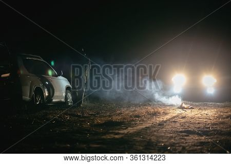 Suv Stuck In A Swamp At Night And Car Headlights.