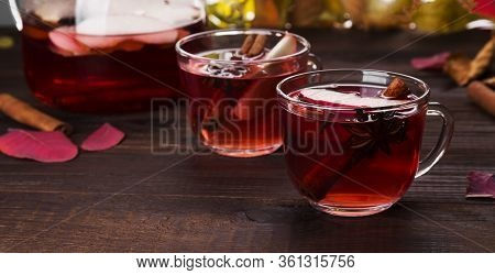 Hot Drink With Hibiscus Red Tea With Apple, Cinnamon And Anise In Glass Teapot And Two Glasses On Wo