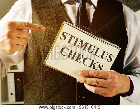 Man Holds Information About Coronavirus Stimulus Checks.