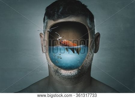 Surreal Portrait Of Man With Cropped Face Filled With Water With A Fish Inside On A Blue Background.