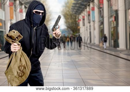 Hooded Robber With A Gun And A Bag Of Money In The City