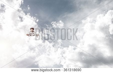 Young Little Boy Keeping Eyes Closed And Looking Concentrated While Meditating On Clouds In The Air