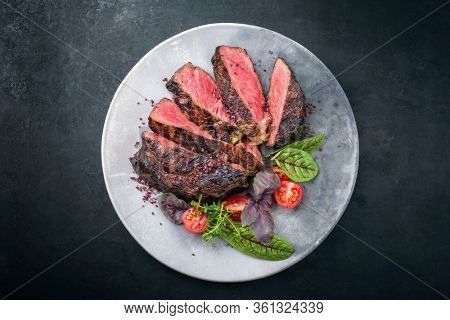 Barbecue dry aged wagyu entrecote beef steak with lettuce and tomatoes as top view on a modern design plate with copy space