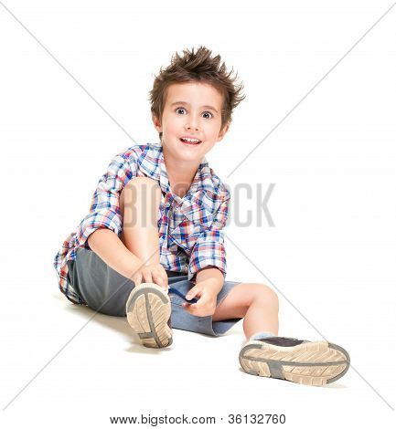 Naughty Hairy Little Boy In Shorts And Shirt Putting On Shoes