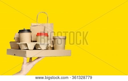 Hand Holding Various Take-out Food Containers, Pizza Box, Coffee Cups In Holder And Paper Bag On Yel