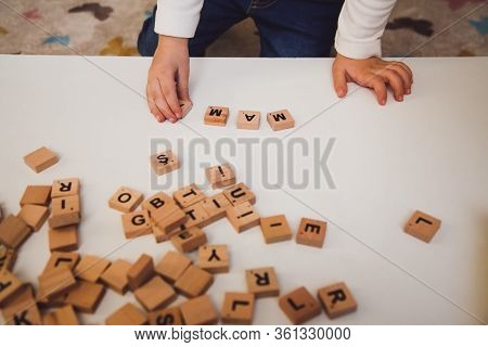 Child Hands With Wooden Letters On The White Table. Child Playing At The Table. Early Development Of