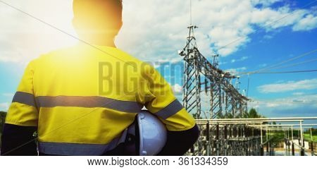 Engineer In Yellow Uniform, And Holding A White Hat, Standing To Look At The Structure Of The Substa