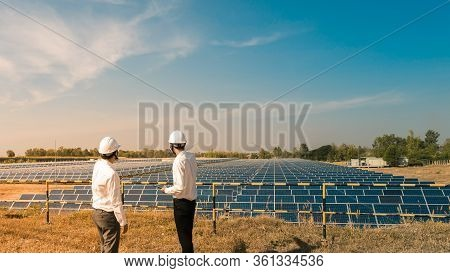 The Solar Farm(solar Panel) With Two Engineers Are Talk About The Production Capacity, Alternative E