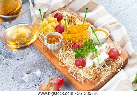 Assorted Cheese On A Wooden Background And A Glass Of White Wine