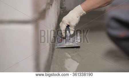Waterproofing The Leveling Floor With A Spatula. An Industrial Worker At A Construction Site Install