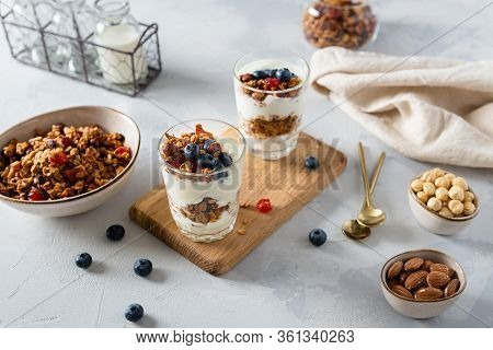 Morning Granola Breakfast With Raisins, Cranberries And Hazelnuts Served With Yogurt In Glasses On A
