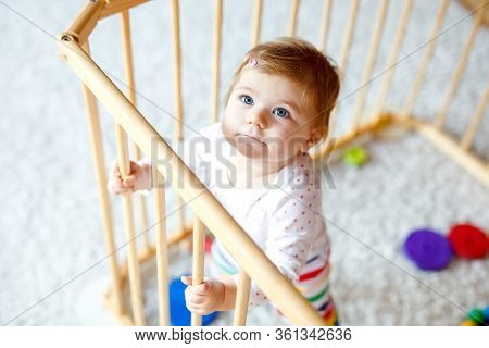 Beautiful Little Baby Girl Standing Inside Playpen. Cute Adorable Child Playing With Colorful Toys.