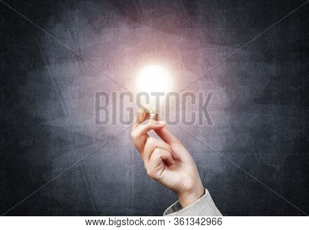 Human Hand With Glowing Incandescent Lamp On Background Grunge Wall. Electricity Power Generation Sy