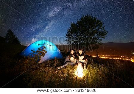 Young Couple Having A Rest At Bonfire Beside Camp And Blue Tourist Tent, Drinking Tea, Enjoying Nigh