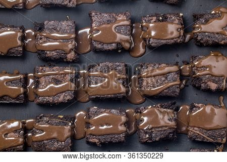 Chocolate Cake Brownie Squares Dribbled With Chocolate Ganache Sauce Isolated On Black Texture Backg
