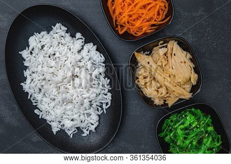 Rice With Korean Carrots, Soy Asparagus And Chuka On Black Background Top View.