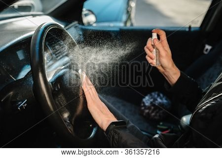 Spraying Antibacterial Sanitizer Spray On Steering Wheel Car, Infection Control Concept. Prevent Cor