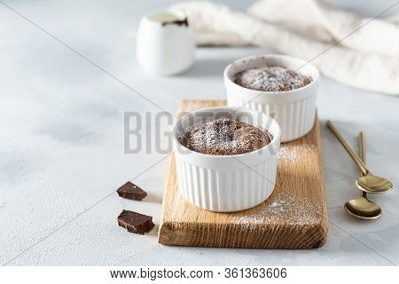 Chocolate Lava Cake With Liquid Centre In White Ramekins On Wooden Board. Confectionery, Cafe, Resta