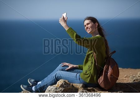 Happy Girl Traveler With A Backpack Takes A Selfie On A Smartphone On The Background Of The Sea And