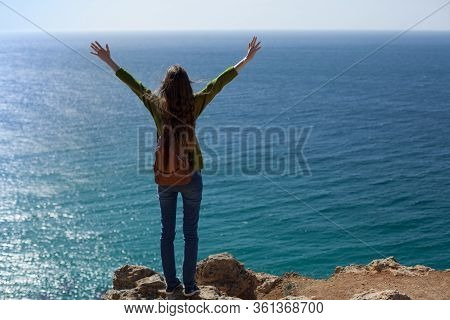 A Young Female Traveler With A Backpack On A Cliff On The Sea, Stands With Her Hands Up. The Concept